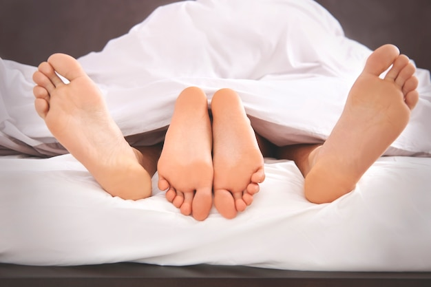 Blote menselijke voeten steken uit het bed