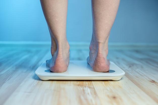 Blote voeten van vrouwen staan op de elektronische weegschaal op de grond om het gewicht van het lichaam te controleren en de set van extra kilo's in het blauwe licht te regelen