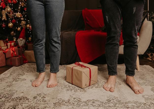 Blote voetenbenen in spijkerbroek, mannen en vrouwen in het midden van een ingepakt cadeau vastgebonden met een lint