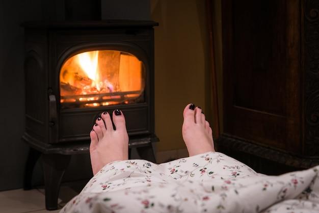 Blote vrouw voeten bij de gezellige open haard binnen op een koude winteravond.