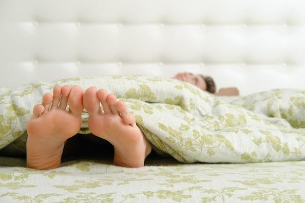 Blote vrouwelijke voeten met lange tenen die onder de deken uitsteken