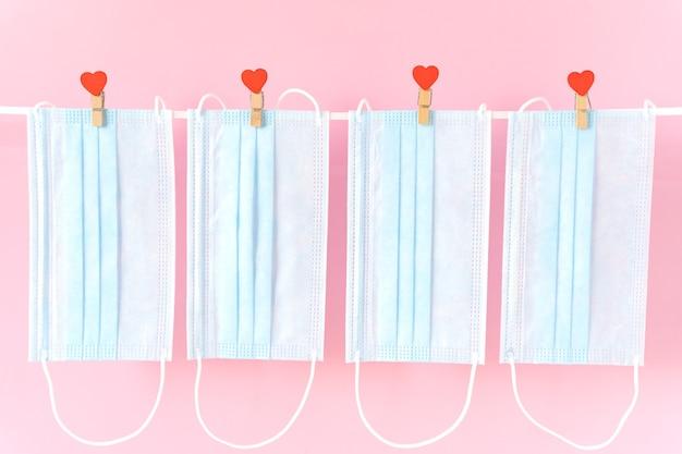 Blu beschermende gezichtsmaskers die op wasknijpers met hartjes op koord hangen
