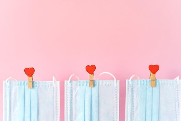 Blu beschermende gezichtsmaskers vliegen op wasknijpers met hartjes op touw.