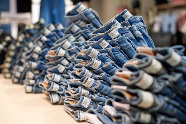 Blue denim jeans stapelen op houten tafel bovenop in kledingwinkel in modern winkelcentrum. gevouwen katoenen jeans op etalage.