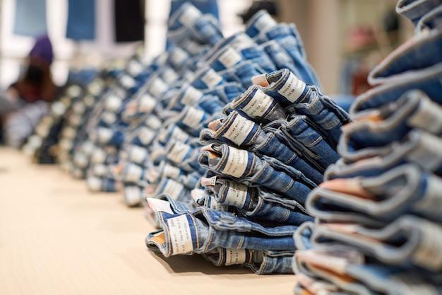 Blue denim jeans stapelen op houten tafel bovenop in kledingwinkel in modern winkelcentrum