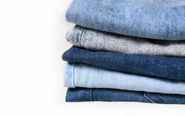 Blue denim jeans textuur. gebruikte verschillende jeans gestapeld in een stapel geïsoleerd op een witte achtergrond
