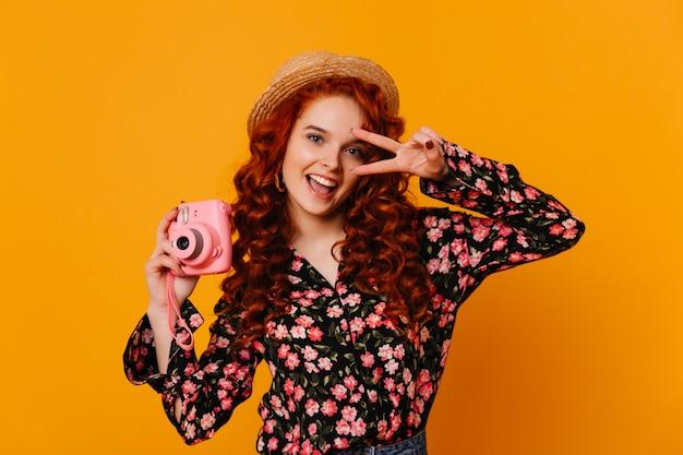 Blue-eyed cutie vrouw met rood haar glimlacht en tintelt vredesteken, met roze camera op geïsoleerde ruimte.