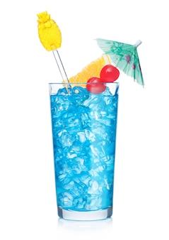 Blue lagoon cocktail longdrinkglas met roerder en sinaasappelschijfje met zoete kers en paraplu op witte achtergrond. mix van wodka en blue curacao likeur.