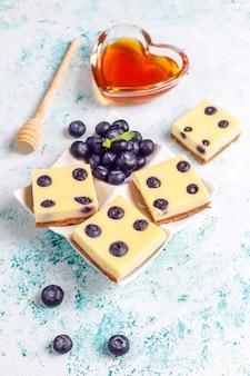 Blueberry cheesecake bars met honing en verse bessen.