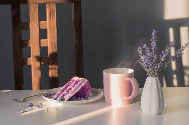 Blueberry lavendel cheesecake op bord en kopje thee op witte tafel