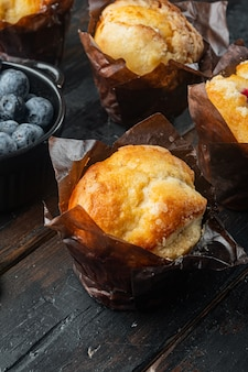 Blueberry muffins met verse bessen, op oude donkere houten tafel achtergrond