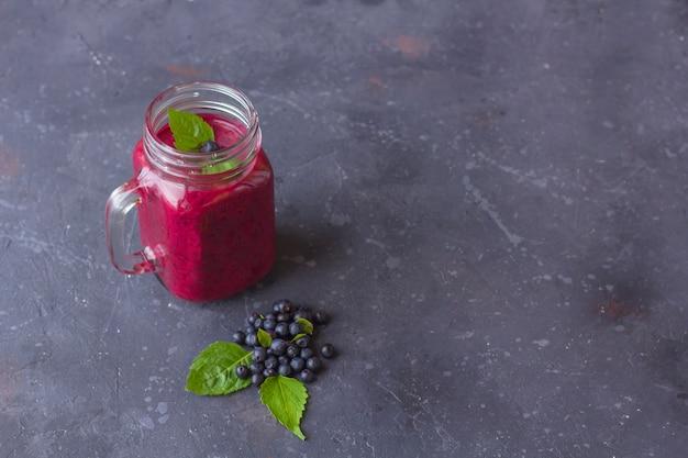Blueberry smoothie in mason jar mok met munt en wat verse bessen. het concept van goede voeding en gezond eten. biologische en vegetarische drank. close-up, kopieer ruimte voor tekst