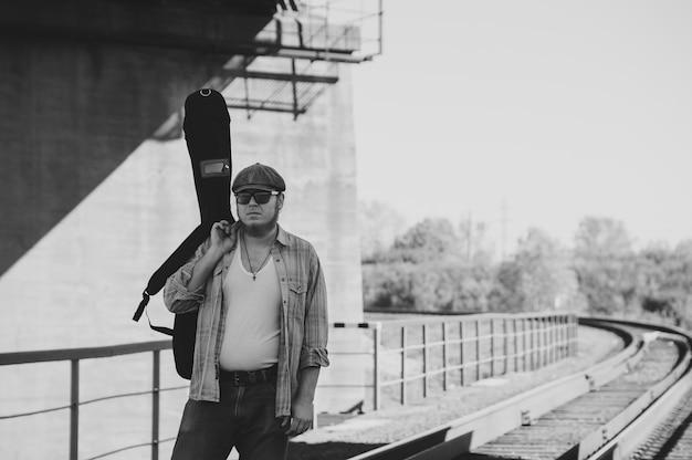 Bluesman met gitaarkoffer loopt op spoorweg. bluesmuzikant op spoorweg in grijswaarden. coole kerel met gitaar. bebaarde man reist licht.