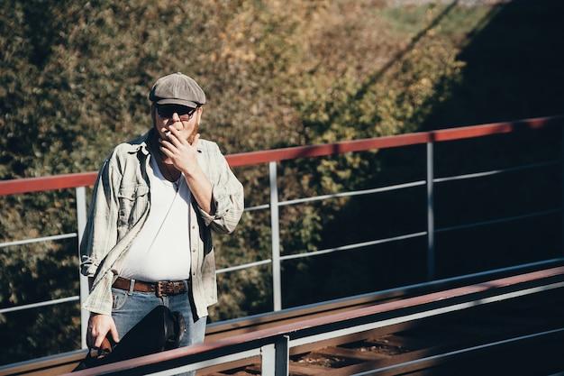 Bluesman met gitaarkoker rookt sigaretten op spoorweg. bluesmuzikant met sigaret op spoorweg. coole kerel met gitaar.