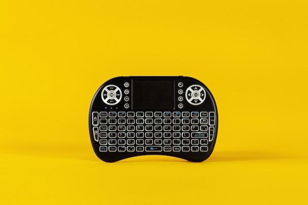 Bluetooth toetsenbord afstandsbediening. gele achtergrond. ruimte voor teksten.