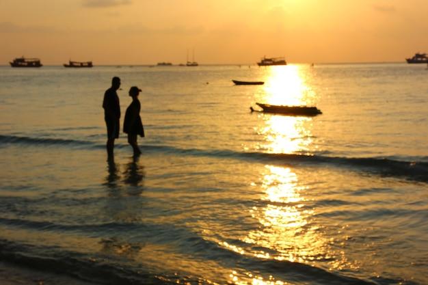 Blur foto van silhouet paar op het strand in zonsondergang tijd, minnaar viert op valentijnsdag door liefde te zeggen en voor te stellen. man en vrouw gaan trouwen zijn pre-huwelijk op het strand in de beste tijd.
