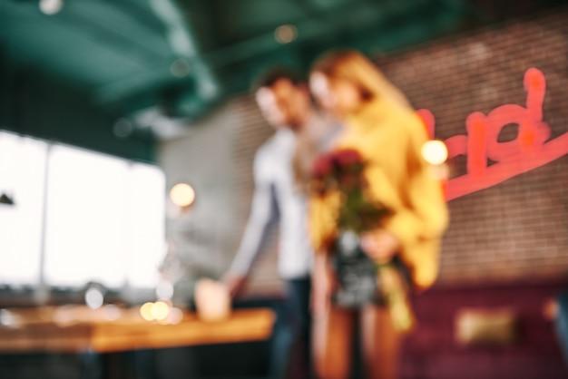 Blured restaurant interieur voor achtergrond. paar gaan aan een tafel bij het raam zitten. romantische lunch of diner voor twee. wazig hotel restaurant interieur