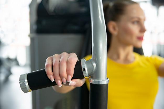 Bluredportret van het jonge kaukasische vrouw uitwerken op oefeningsmachine binnen gymnastiek