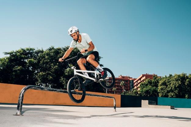 Bmx rijder die trucs in skatepark uitvoert
