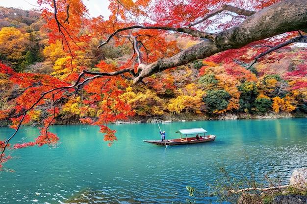 Boatman punteren de boot op de rivier. arashiyama in de herfstseizoen langs de rivier in kyoto, japan