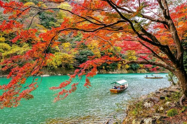 Boatman punteren de boot op de rivier. arashiyama in de herfstseizoen langs de rivier in kyoto, japan.