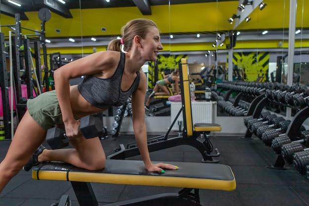 Bochtige fitte jonge vrouw die halter optilt met één arm in een sportschool