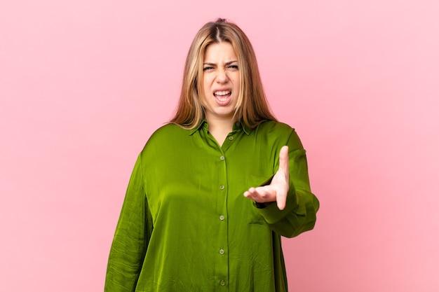 Bochtige mooie blonde vrouw die boos, geïrriteerd en gefrustreerd kijkt