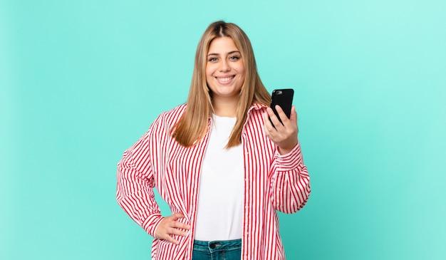 Bochtige mooie blonde vrouw die gelukkig glimlacht met een hand op de heup en zelfverzekerd en een smartphone vasthoudt