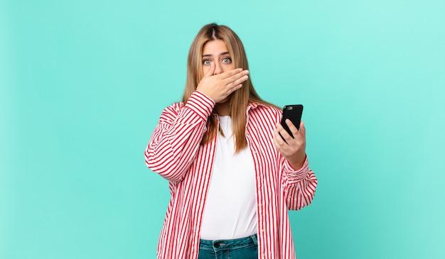 Bochtige mooie blonde vrouw die mond bedekt met handen met een geschokte en een slimme telefoon vasthoudt