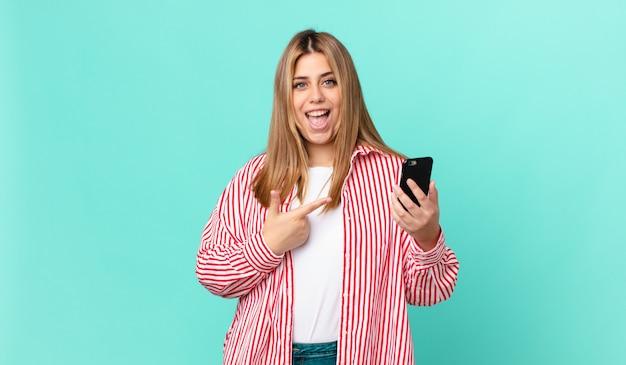 Bochtige mooie blonde vrouw die opgewonden en verrast kijkt en naar de zijkant wijst en een smartphone vasthoudt