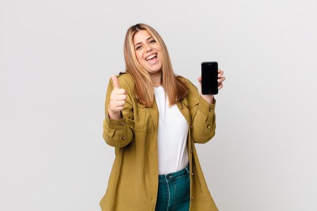 Bochtige mooie blonde vrouw die trots is, positief glimlacht met duimen omhoog en een smartphone vasthoudt