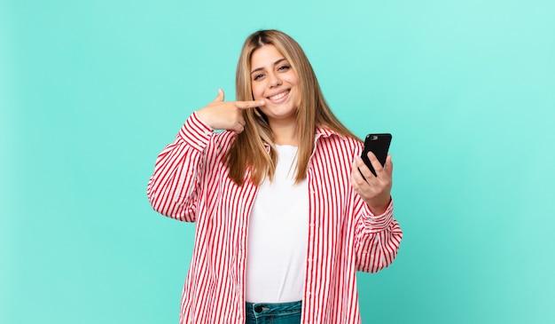 Bochtige, mooie blonde vrouw die zelfverzekerd glimlacht, wijst naar haar eigen brede glimlach en houdt een smartphone vast