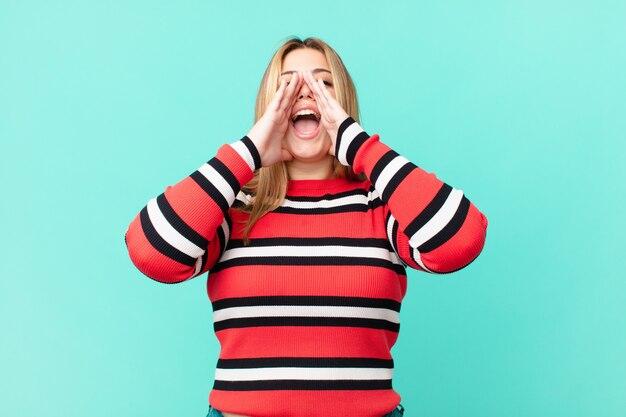 Bochtige mooie blonde vrouw die zich gelukkig voelt, een grote schreeuw geeft met de handen naast de mond