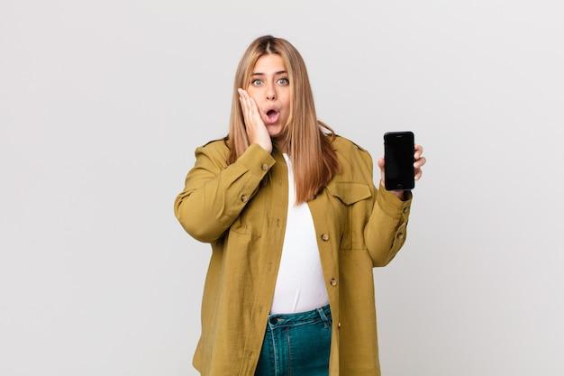 Bochtige mooie blonde vrouw die zich geschokt en bang voelt en een smartphone vasthoudt