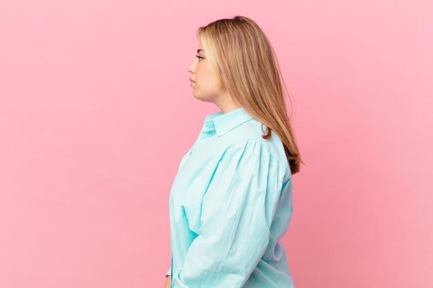 Bochtige mooie blonde vrouw op profielweergave denken, fantaseren of dagdromen
