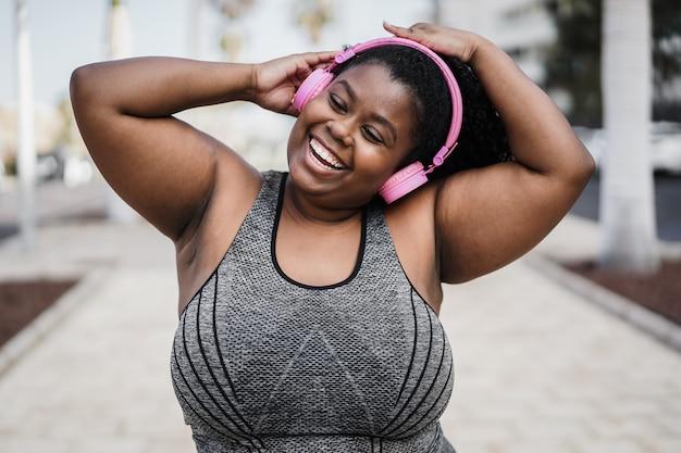 Bochtige vrouw danst en luistert naar muziek met een koptelefoon terwijl ze buiten jogt in het stadspark - focus on face