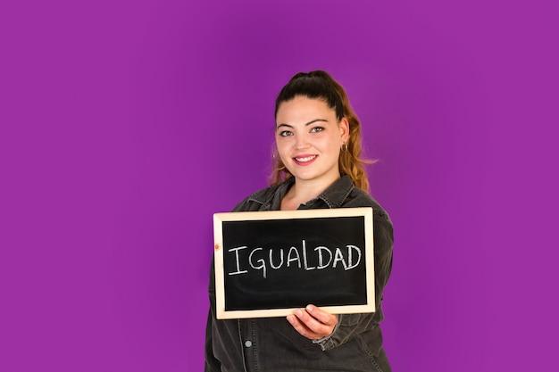 Bochtige vrouw die een klein bord met gelijkheidswoord houdt, schrijft daarin gelijkheid