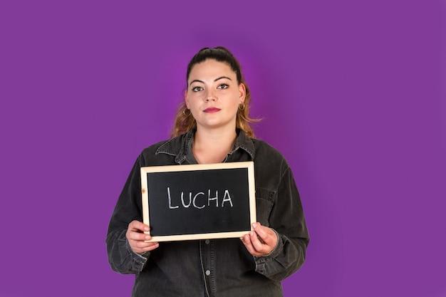 Bochtige vrouw die een klein bord met lucha-woord houdt, schrijft daarin strijd
