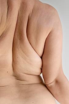 Bochtige vrouw die zelfverzekerd naakt poseert en haar huid laat zien