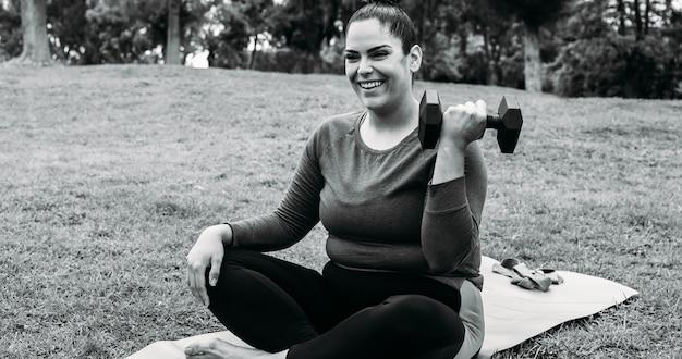 Bochtige vrouw doet trainingsroutine buiten in het stadspark - focus op gezicht
