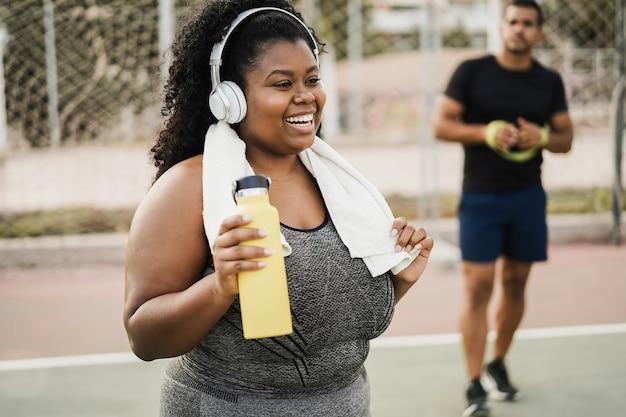 Bochtige vrouw doet workout ochtendroutine buiten in het stadspark