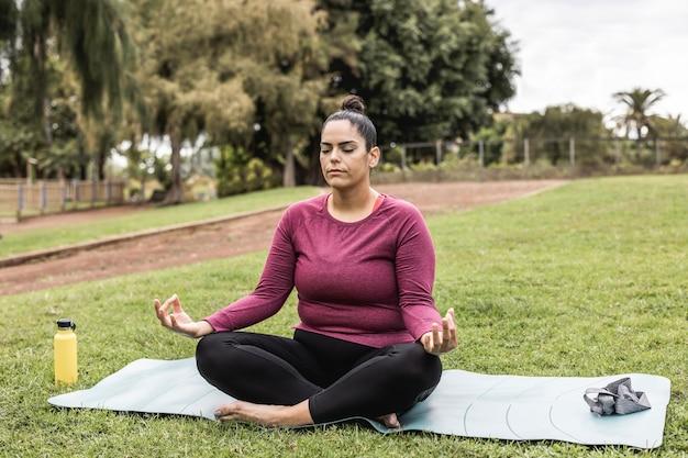 Bochtige vrouw doet yoga meditatie buiten in stadspark - focus op gezicht