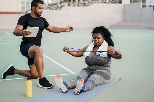 Bochtige vrouw en personal trainer doen pilates-trainingssessie buiten - hoofdfocus op meisjesgezicht