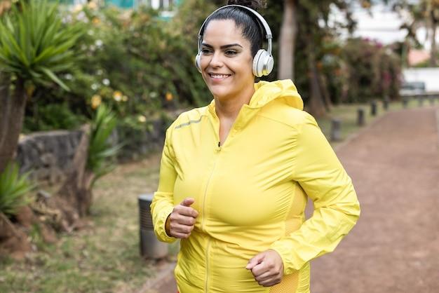 Bochtige vrouw joggen buiten bij stadspark - plus grootte en training oefeningen concept