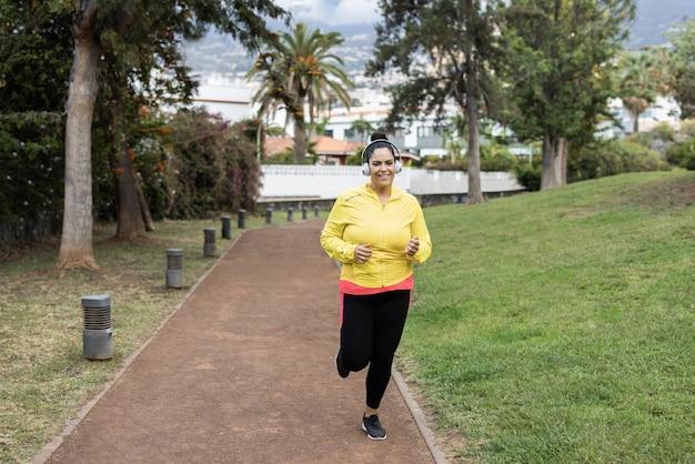 Bochtige vrouw joggen buiten bij stadspark