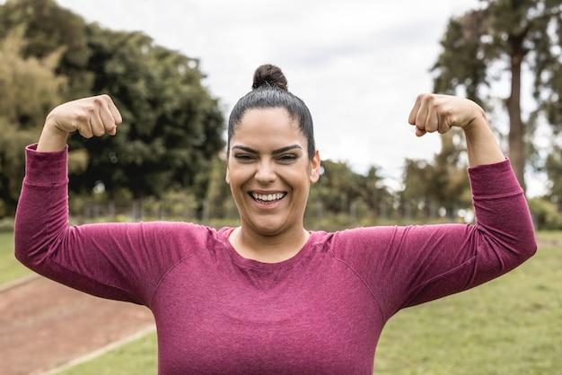 Bochtige vrouw lachend op de camera tijdens het joggen routine buiten in het stadspark - focus op het gezicht
