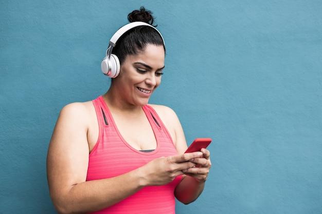 Bochtige vrouw luistert afspeellijstmuziek met mobiele telefoon na het joggen in de buitenlucht - focus on face