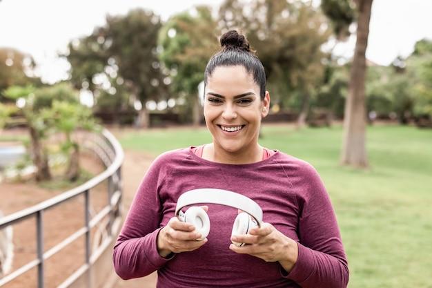 Bochtige vrouw luistert afspeellijstmuziek na het joggen in de buitenlucht - focus on face