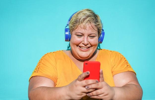 Bochtige vrouw met behulp van smartphone buiten - jonge vrouw met plezier luisteren muziek afspeellijst op mobiele telefoon