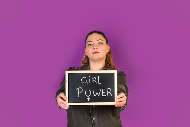 Bochtige vrouw met een klein bord met de zin van de meisjesmacht erin schrijven
